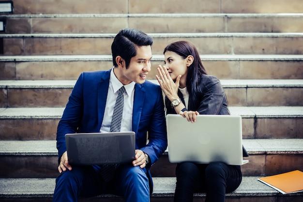 Die jungen geschäftspaare, die auf dem treppenhaus einige arbeiten vorher sitzen, arbeiten an laptop.