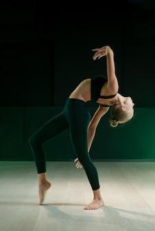 Die jungen mädchen tanzen im studio auf dunklem hintergrund