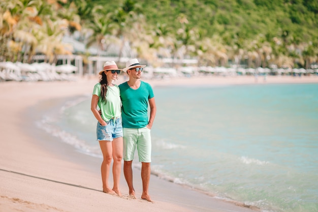 Die jungen paare, die auf tropischen strand mit weißem sand- und türkisozean gehen, wässern in antigua-insel in karibischen meeren