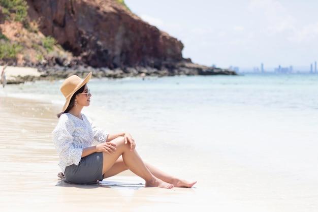 Die jungen reisenden frauen entspannen sich auf dem strand auf sommer