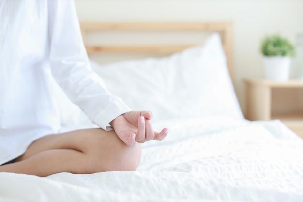 Die jungen und schönheitshände, die herein genießen, meditieren mit yogahaltung auf hölzernem bett im modernen schlafzimmer mit rechtem kopienraum