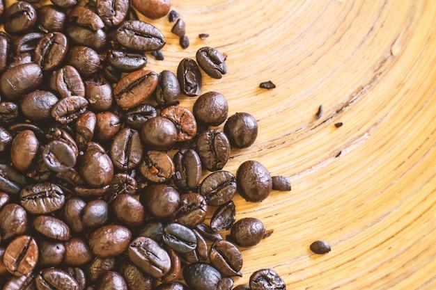 Die kaffeebohnen auf hölzerner platte