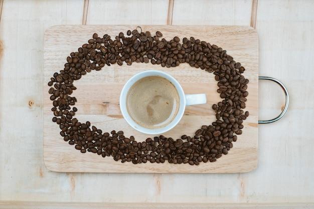 Die kaffeebohnen werden um die kaffeebecher auf der tafel gekapselt.