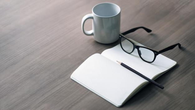Die karriere des verfassers auf dem schreibtisch mit einer weißen kaffeetasse, einem bleistift und einem glasbuch