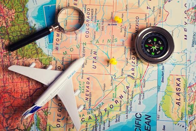 Die karte, das flugzeug und das zeug auf einem holztisch