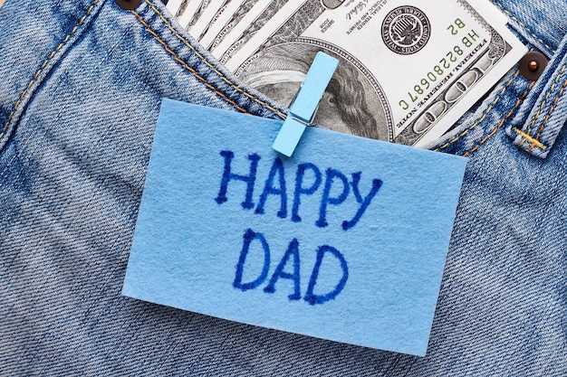 Die karte und das geld des glücklichen vaters. stoffgrußkarte auf jeans. bargeld ist ein perfektes geschenk.