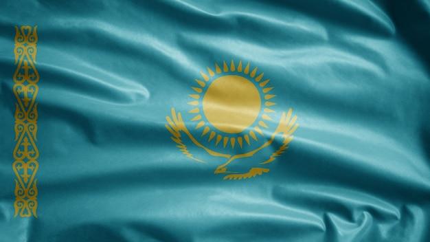 Die kasachische flagge weht im wind. nahaufnahme von kasachstan banner weht, weiche und glatte seide. stoff textur fähnrich hintergrund.