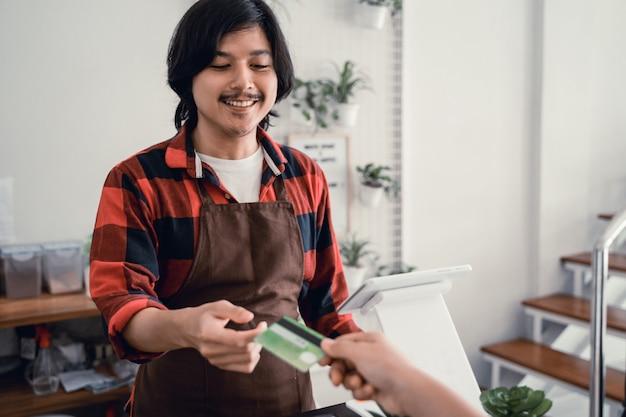 Die kassiererin im café akzeptiert kreditkartenzahlungen