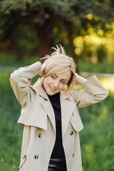 Die kaukasische blonde frau trägt ein grabenlächeln glücklich am sonnigen frühlingstag draußen, der im park geht Premium Fotos