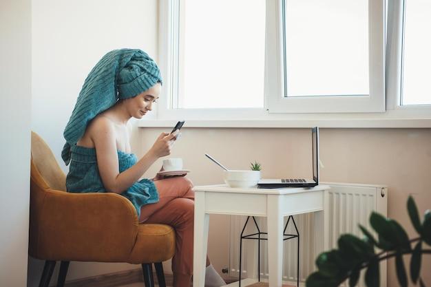 Die kaukasische dame plaudert nach dem baden auf einem handy, trägt ein handtuch auf dem kopf und trinkt einen tee