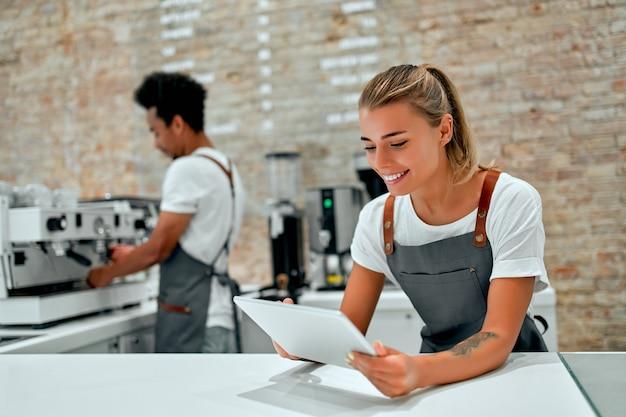 Die kaukasische frau barista steht mit einer tablette in den händen an der theke in einem café.