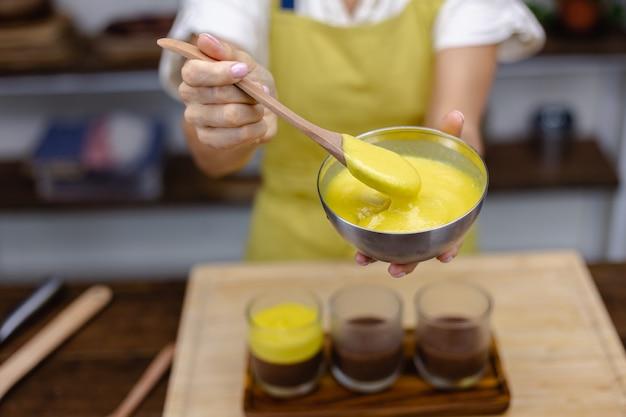 Die kaukasische frau in der küche macht chia-pudding mit mangomarmelade. wüste aus mandelmilch, chiasamen, kakao, mangomarmelade und müsli.