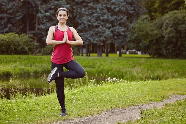 Die kaukasische frau macht übungen im öffentlichen park.