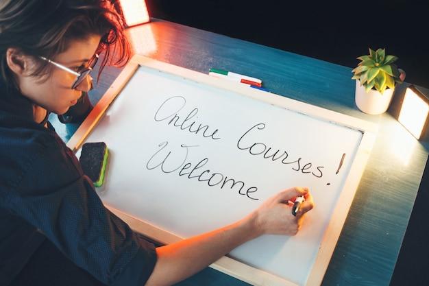 Die kaukasische frau schreibt die begrüßung von online-kursen an eine tafel, bevor sie mit dem unterricht beginnt