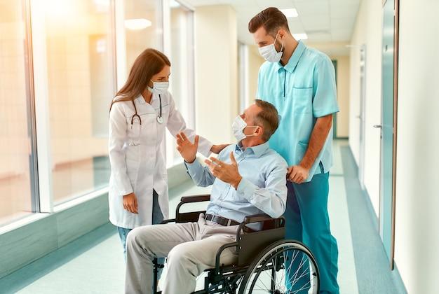 Die kaukasische krankenschwester und der hübsche junge arzt, die chirurgische masken tragen, um sich vor einer pandemie zu schützen, kümmern sich um einen reifen männlichen patienten, der in einem rollstuhl in einem krankenhaus sitzt.