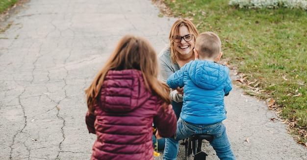 Die kaukasische mutter, die eine brille trägt, jubelt ihren kindern während eines familienausflugs zu
