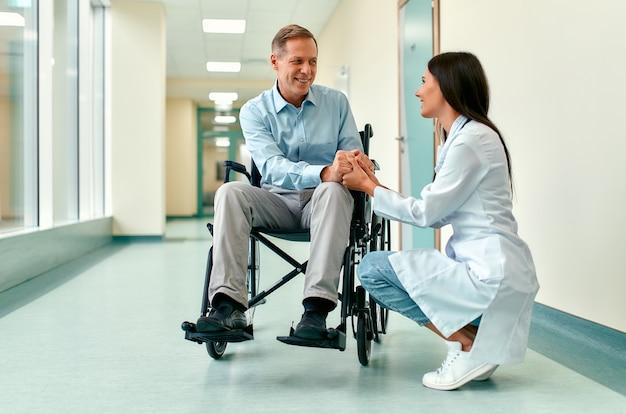 Die kaukasische schöne krankenschwester in der medizinischen uniform kümmert sich um einen reifen männlichen patienten, der auf einem rollstuhl im krankenhaus sitzt und seine hände hält.