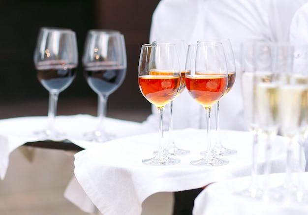 Die kellner begrüßen die gäste mit alkoholischen getränken. champagner, rotwein, weißwein auf tabletts.