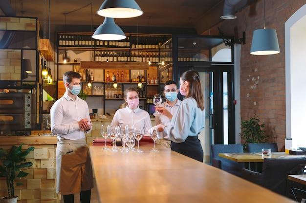 Die kellner des restaurants in einer medizinischen maske lernen, zwischen den gläsern zu unterscheiden.