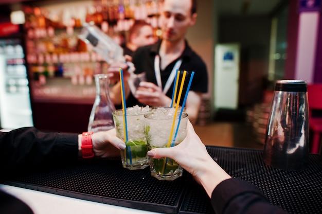 Die kellnerhände, die mojito coctails halten, trinken hintergrundbarmann bei der arbeit