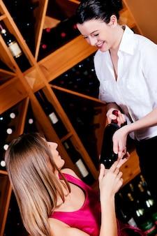 Die kellnerin bietet eine flasche rotwein an
