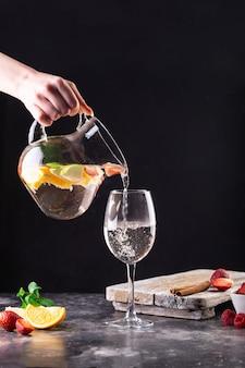 Die kellnerin, die eine karaffe in der hand hält, gießt frische limonade in ein glas