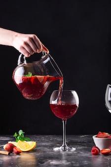 Die kellnerin, die eine karaffe in der hand hält, gießt heißen glühwein in ein glas
