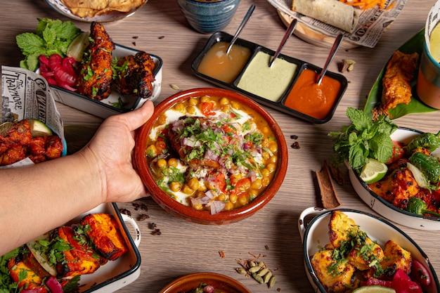 Die kellnerin legt den samosa chana chaat teller auf den tisch. kulinarisches fest. indische küche. vielzahl von gerichten