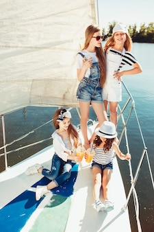 Die kinder an bord der seelyacht trinken orangensaft. die teenager- oder kindermädchen gegen blauen himmel im freien.