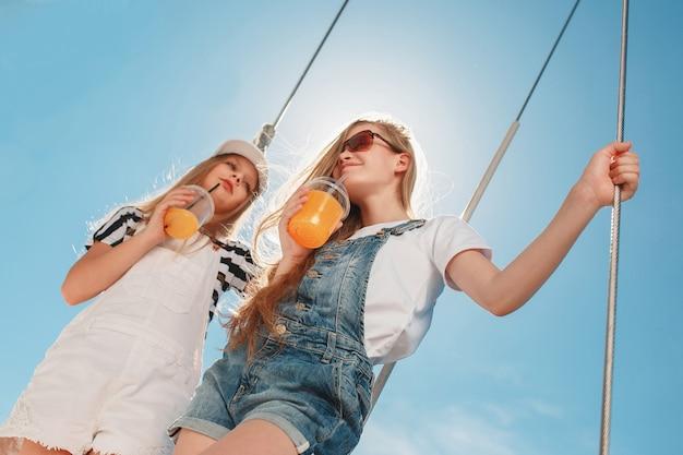 Die kinder an bord der seelyacht trinken orangensaft