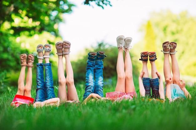 Die kinder, die auf grünem gras im park an einem sommertag mit ihren beinen liegen, hoben zum himmel an.