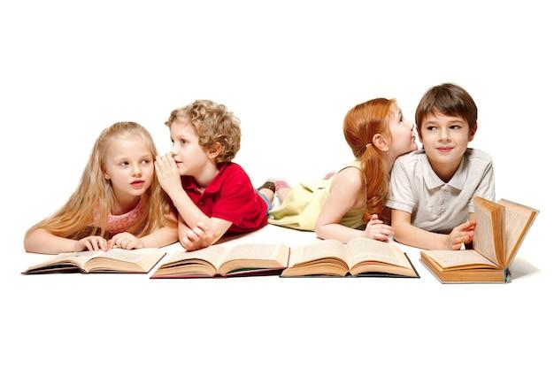 Die kinder jungen und mädchen mit büchern im studio, lächelnd, lachend, isoliert auf weiss. tag des buches, der bildung, der schule, des kindes, des wissens, der kindheit, der freundschaft, des studiums und des kinderkonzepts