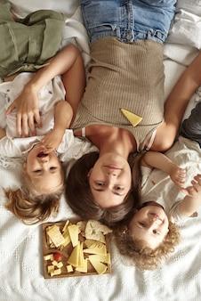 Die kinder liegen mit ihrer mutter auf dem bett und essen käsestücke.