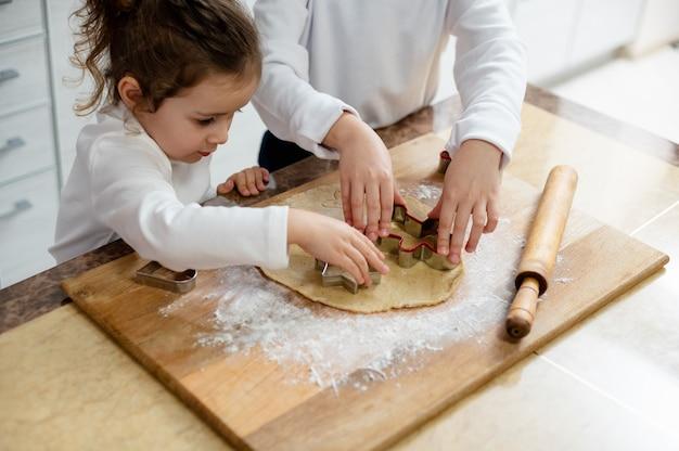 Die kinder schneiden mit den speziellen formen aus den weihnachtsplätzchen