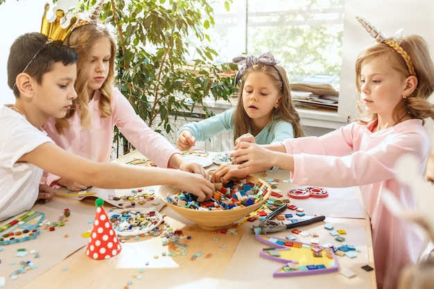 Die kinder und geburtstagsdekorationen. die jungen und mädchen am tisch mit essen, kuchen, getränken und party-gadgets.