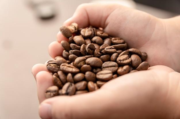 Die kinderhände, die kaffee machend herz halten, bilden sich auf dem leben