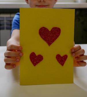 Die kinderhände machen eine karte aus einem herzen aus papier nahaufnahme ein geschenk zum vatertag