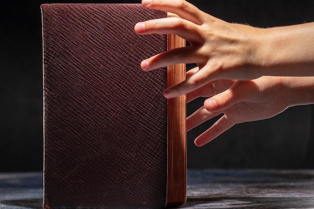 Die kinderhände strecken sich zum alten buch. das konzept des wissensdursts.