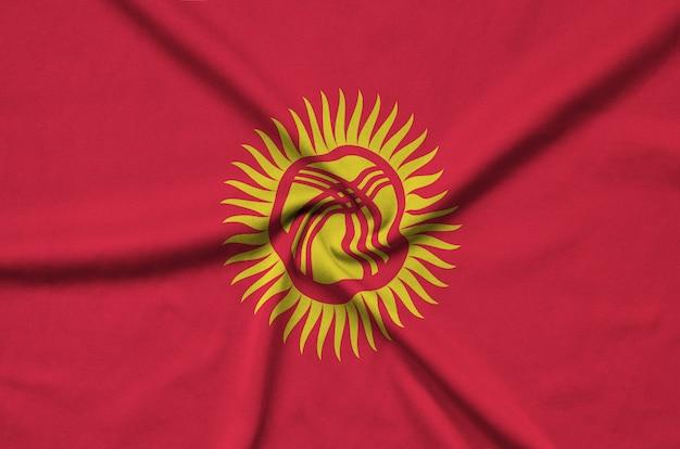Die kirgisische flagge ist auf einem sportstoff mit vielen falten abgebildet.