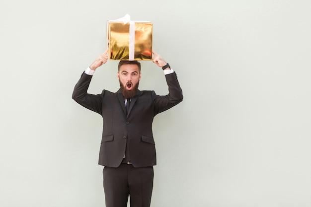 Die kiste balanciert auf dem kopf eines erstaunten geschäftsmannes. studioaufnahme