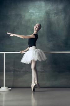 Die klassische ballerina posiert an der ballettstange
