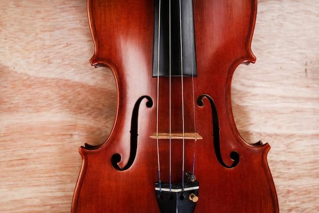 Die klassische geige setzt auf holzbrett, zeigt die vorderseite des akustischen instruments