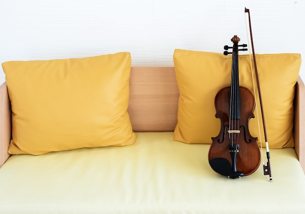 Die klassische geige und bogen auf holzstuhl, vor gelbem kissen