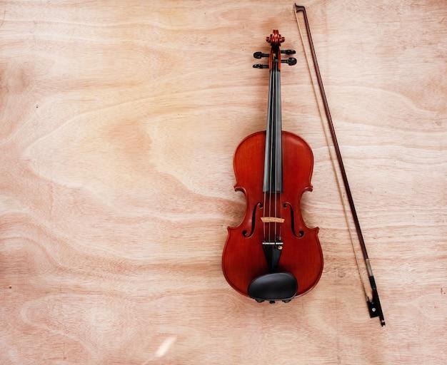 Die klassische violine und der bogen setzen auf holzbrett
