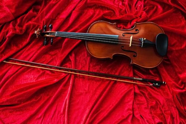 Die klassische violine und der bogen setzen auf roten stoffhintergrund, zeigen detail des instruments