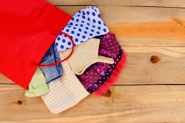 Die kleidung der frauen fällt aus papiereinkaufstaschen auf hölzernem hintergrund heraus.