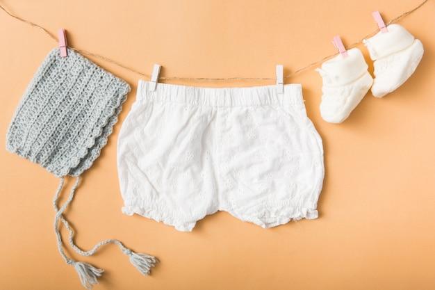 Die kleidung des babys, die an der wäscheleine mit wäscheklammer hängt