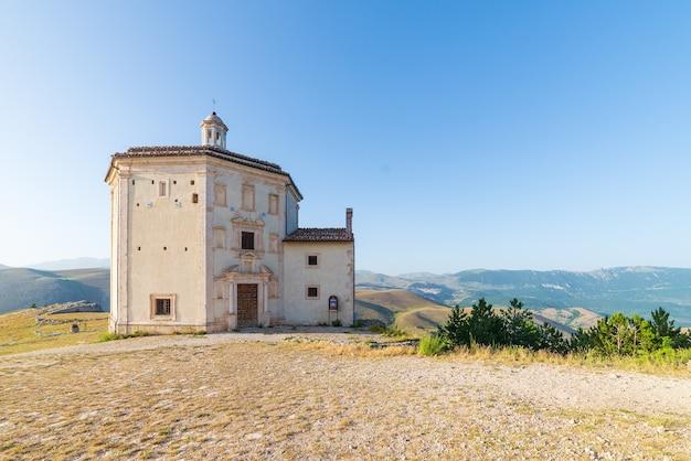 Die kleine achteckige kapelle in der nähe der burgruine rocca calascio bei sonnenuntergang im gegenlicht, wahrzeichen im nationalpark gran sasso, abruzzen, italien. berge malerischen hintergrund.