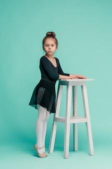 Die kleine balerina-tänzerin an der blauen wand