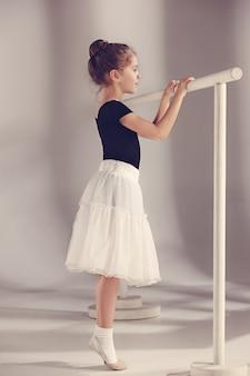 Die kleine balerina-tänzerin an der grauen wand
